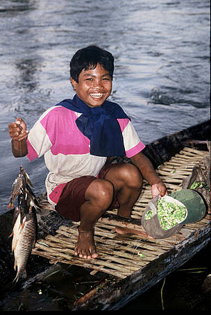 Tribal boy collects family supper: wild flowers and fish from the Serepok River in the Mekong River ...  	© WWF / Elizabeth KEMF