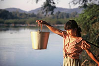 Tribal girl collecting water from the Srepok River, Vietnam.  	© WWF / Elizabeth KEMF