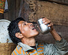 Surya Bahadur Gurung from Huslangkot of Dharampani in Tanahu District gulps down a pitcher full of water that his wife fetched from the newly established tap in their village.