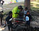 A community representative helps children of Vatutavui pot mangrove propergules.