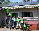 A family stands in front of their solar panels connecting the dots to a renewable energy solution.