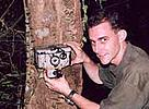 Barney Long rigging a camera trap in the forest.  	© WWF