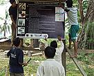 COMFISH staff work with villagers from Ban Muong Muan to nail down a sign board explaining village regulations.