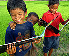 Three Khmer boys reading fish conservation book. On the banks of the Tonle Sap River, Cambodia.