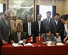 Ms. Yin Hong, Deputy Administrator of State Forests Administration, People's Republic of China and Mr. Yuba Raj Bhusal, Secretary of Ministry of Forests and Soil Conservation Government of Nepal signing the MOU in the presence of Honorable Minister Mr. Deepak Bohara, Minister of Forests and Soil Conservation, Government of Nepal. They are surrounded by the Nepali and Chinese delegation.