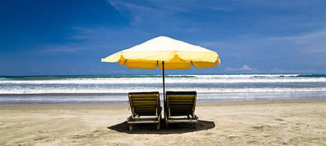Empty sun chairs with yellow umbrella at the Seminyak beach, Bali, Indonesia.  rel=