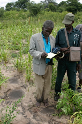 Local farmer Moses Maseku is made to sign the protocol in the Conservancy's Event Book by an ...  	© WWF / Folke WULF