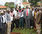 Geoffrey Ayeni is joined by the Minister of Water and Environment, district officials, WWF Uganda Country Director and other well-wishers in the planting of a tree seedling.
