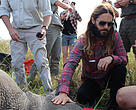 Jared Leto kneeling next to a southern white rhino andassisting with the collaring at andBeyond Phinda Game Reserve