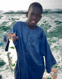 Child holding fish, M'Bour, Senegal