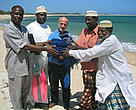 Dr kwame Koranteng (left), WWF EARPO regional representative, presents sustainable fishing gear to local fishermen living around Kiunga Marine Reserve.
