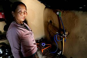 Laxmi Rana showing biogas in her kitchen