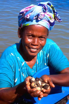 Woman collecting sea food in the tidal marshes of Nosy Be Island, Madagascar.  	© WWF / Hartmut JUNGIUS