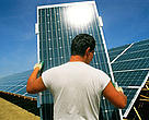 Man holding solar panel covered with photovoltaic cells at solar park, Leipzig, Germany.