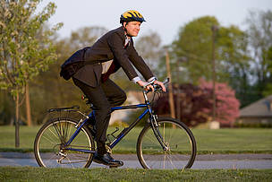 A man in a business suit and biking helmet riding his bicycle to work in a suburban setting