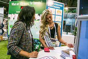 Ilse Saunders, Ms. Earth South Africa 2014, fills out postcard.