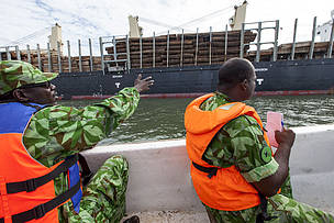 A team of eco-guards from the National Parks Agency Patrols the river estuary. The eco-guards check a chinese ship loaded with uncut timber . It is illegal to export timber from Gabon without processing it in-country