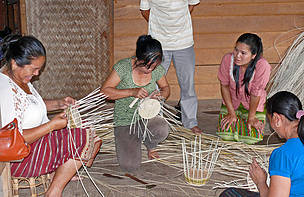 Villagers train in weaving the Easter baskets ordered by Coop