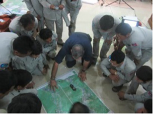 Group analyzing a map of the river at the March 2014 Navigation Training for river guards in Cambodia.