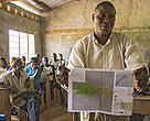 A man in Ilanga, DRC showcases a map his community created of their land and resources.