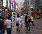 A man using his mobile phone standing in the crowd on Nanjing Road, Shanghai, China.