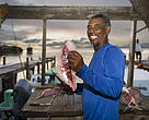 Pany Arceo, a local fisherman cleaning the daily catch. He has lived all his life in Ambergris Caye. About 17,000 people work in the Belize fisheries industry.