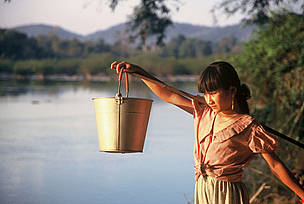 Tribal girl collects water in the evening from the Serepok River in a poor commune in Vietnam's Central Highlands where thousands of poor villagers have access to sanitation.