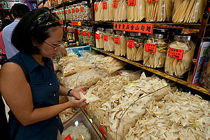 Shoppers looking at dried marine products like shark fins and dried abalone in Sheung Wan District, Hong Kong.