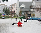 A woman paddling a sea kayak down the middle of a flooded road, Hampton, Virginia, United States.