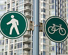 Signs for walking and cycling stand against an urban city backdrop of condominiums in Vancouver, British Columbia, Canada.