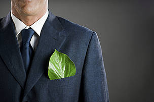 Stylish businessman in a suit and tie with a fresh green leaf in his pocket signals his intent to care about the environment.