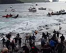Locals wait on the shore to catch and tie up the trapped whales