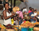 A local woman holds up a dried fish fillet as people pass through the Luangwa Bridge Market, Zambia