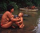 El Niño, Amazon, Brazil. Yanomami, Forest fires. Yanomami Indian woman bathing her child in the river. The Yanomami indians have been adversely affected by the forest fires in the Amazon, they are already facing difficulties enough to keep their traditional lifestyle