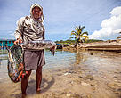 A fisherman holds his catch in Tun Mustapha Park, Kudat, Sabah.