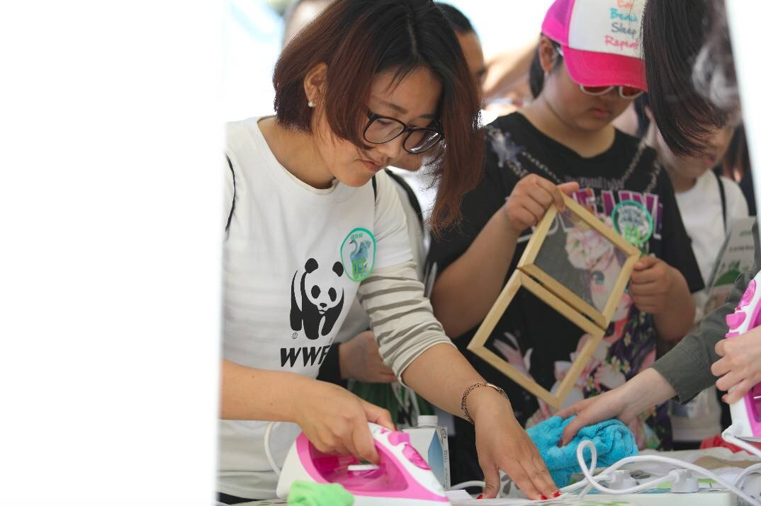 A participant at WWF-China's Green Walk learns about waste recycling.