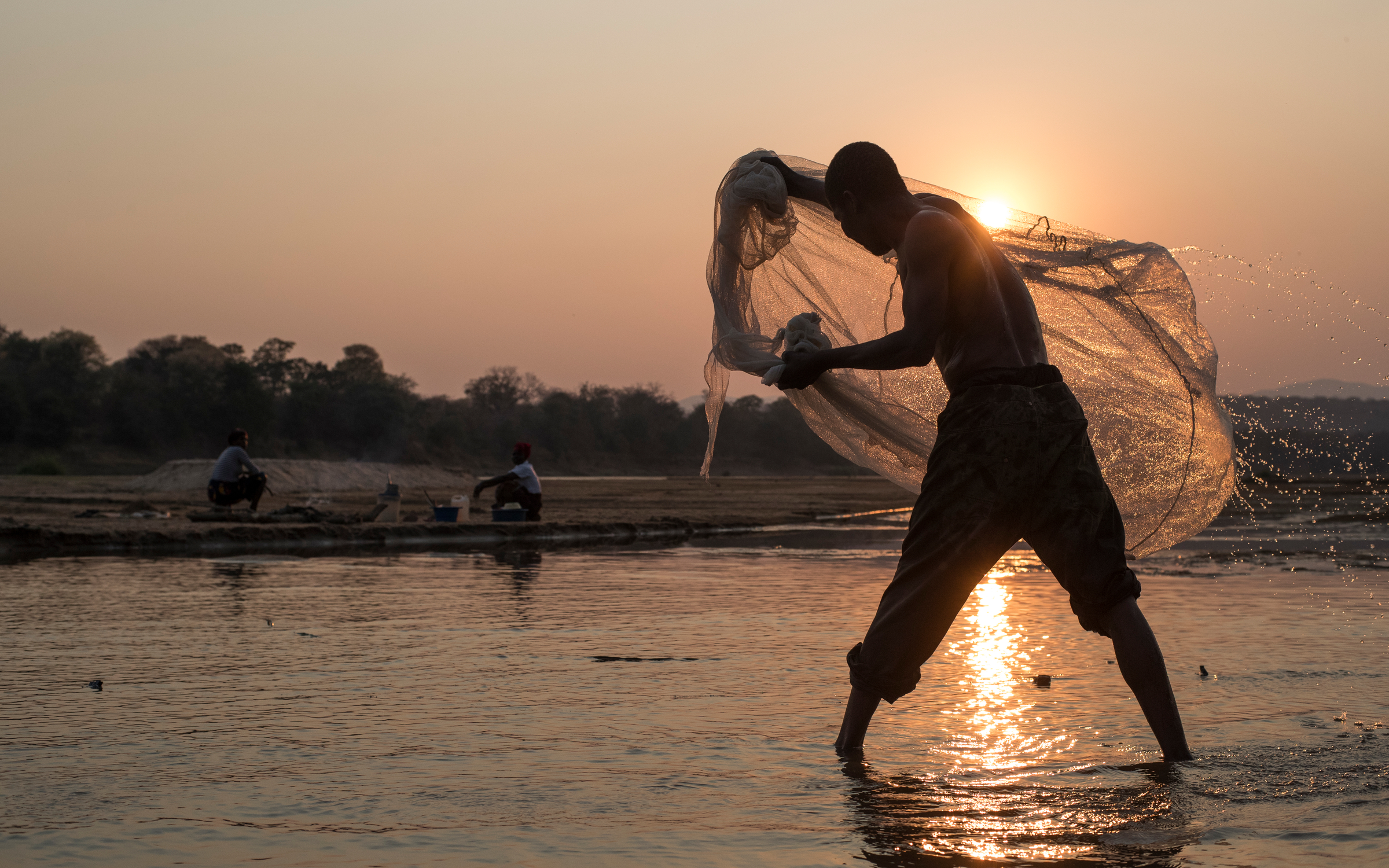 A local fisherman casting his net