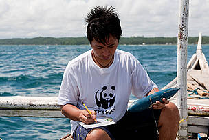 WWF Philippines Donsol Research Coordinator Elson Aca writing down details of a Whale shark satellite tag into his slate. This is a SPLASH Tag deployed in 2007, it records position only for mapping whale sharks' movements. Donsol, Sorsogon, Bicol, Philippines.