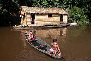Children in a canoe beside their house made of Babassu straw (Orbygnia phalerata) in the Amazon Upland Rainforest, Ayapua¡ community, Piagacu-Purus Sustainable Development Reserve, Ayapua¡ Lake of Purus River, Amazonas State, Brazil.