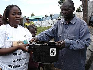 WWF staff member passing out an energy efficient stove in Eastern DRC.  These stoves use less fuel so people rely less on wood from Virunga National Park.