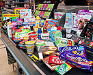 A checkout conveyor belt containg many typical products at a supermnarket in the UK. Cakes, biscuits, chocolate, confectionery, meat, frozen fish, spreads, cereals, sweets, cosmetics, crisps, snacks, cleaning and hygene products amongst the items - Many products contain a surprising amount of Palm Oil.